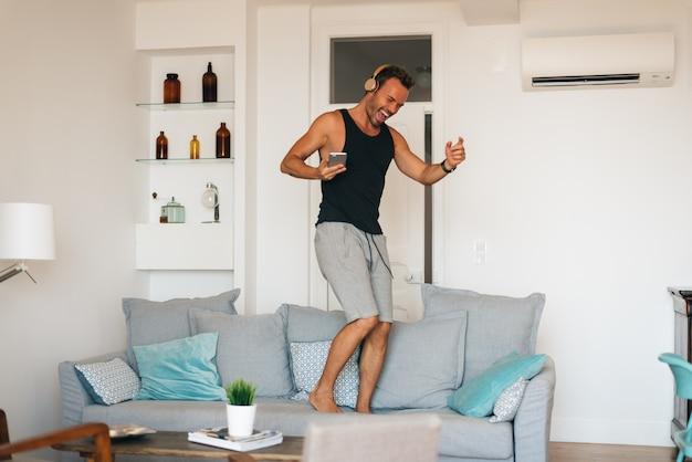 Loira jovem feliz, de pé no sofá em casa, no celular, ouvindo música e dançando