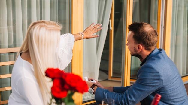 Loira jovem mostrando anel de diamante para seu namorado
