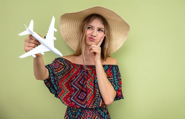 Loira jovem pensativa eslava com chapéu de sol segurando o modelo do avião e olhando para o lado