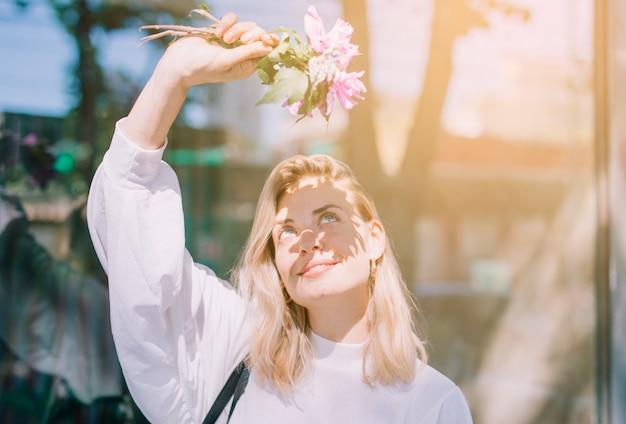Loira jovem segurando flores na mão, protegendo os olhos da luz do sol