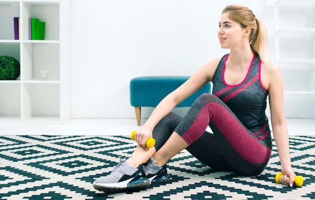 Loira jovem sentada no tapete em casa segurando halteres amarelos na mão