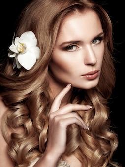 Loira linda com cabelos longos ondulados, tocando o rosto