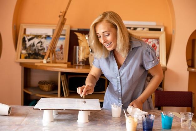 Loira linda com prazer começa a criar foto em seu estúdio, há xícaras com tintas de cores selecionadas na frente dela. ela aplica tinta com espátula. inspiração.