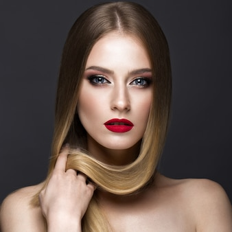 Loira linda com um cabelo perfeitamente liso, maquiagem clássica e lábios vermelhos. rosto bonito