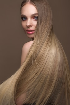 Loira linda com um cabelo perfeitamente liso, maquiagem clássica, rosto de beleza
