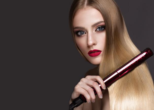 Loira linda com um cabelo perfeitamente liso, ondulação, maquiagem clássica e lábios vermelhos. rosto bonito