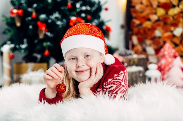 Loira linda com um chapéu de natal posando perto de uma árvore de natal e uma lareira closeup