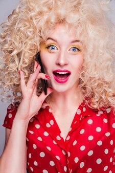 Loira linda com um penteado encaracolado exuberante, maquiagem amarela brilhante nos olhos e uma blusa de bolinhas vermelhas