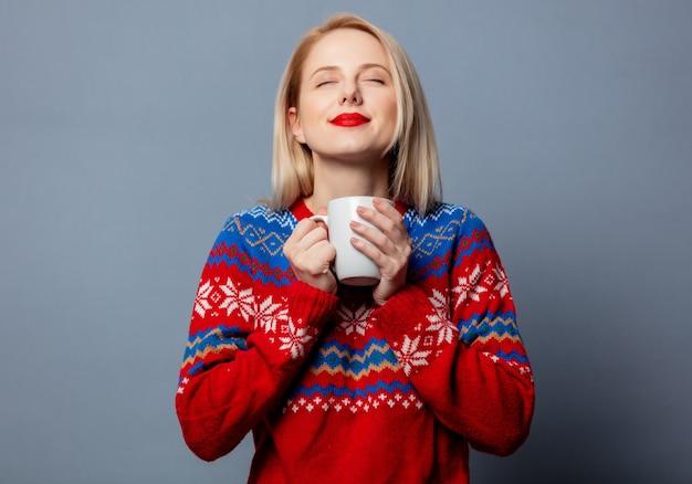 Loira linda com um suéter de natal com uma xícara de café cinza