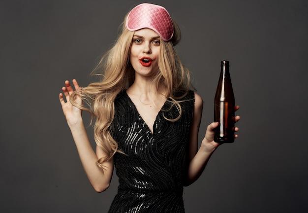 Loira linda com uma máscara de dormir rosa e uma garrafa de cerveja