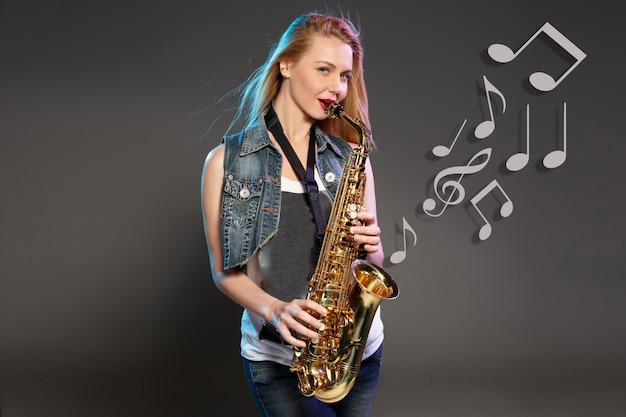 Loira linda como mulher saxofonista em fundo cinza