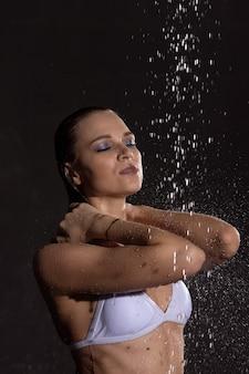 Loira linda e sexy com um corpo perfeitamente tonificado posa em um maiô sob as gotas de água