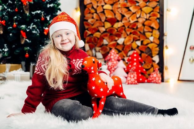 Loira linda em um boné vermelho, brincando com um cervo de natal no interior de um ano novo