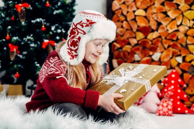 Loira linda em um boné vermelho posando com um presente de natal no interior de um ano novo