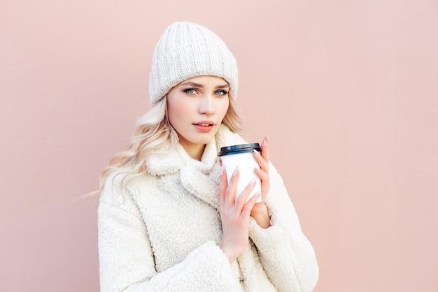 Loira linda em um casaco e chapéu branco detém uma xícara de café