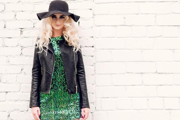 Loira linda em um vestido brilhante e jaqueta de couro no fundo de uma parede de tijolos