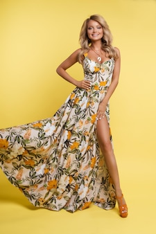 Loira linda em um vestido longo bonito posando