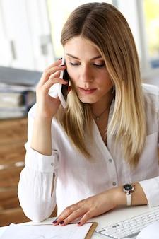 Loira linda empresária pensativa falando no celular no escritório