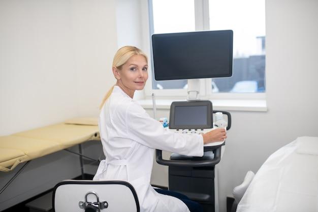 Loira linda especialista em ultrassom com túnica branca sentada na máquina de ultrassom esperando pelo paciente