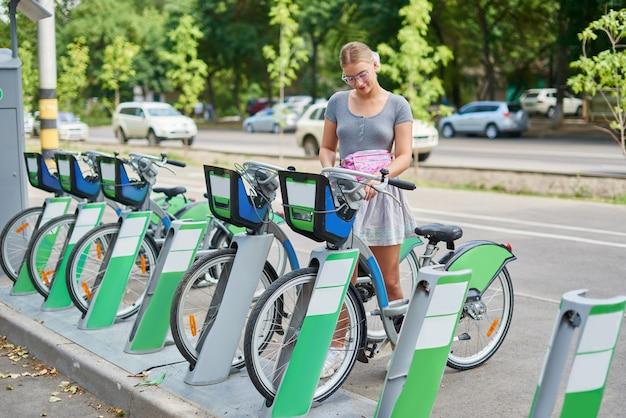 Loira linda garota atlética em uma saia alugar uma bicicleta em almaty