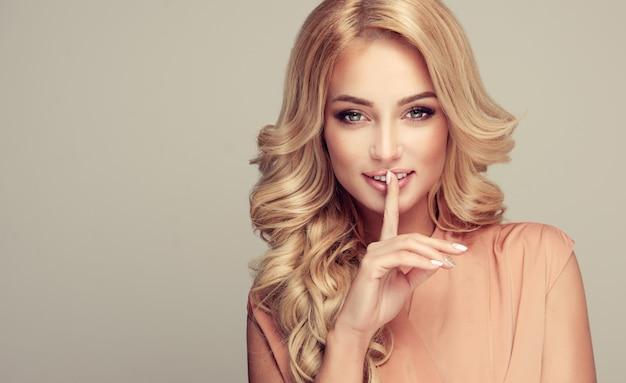 Loira linda garota com um penteado elegante, segurando um dedo na boca com um segredo
