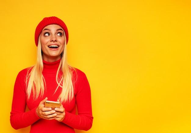 Loira linda garota digita uma mensagem com seu smartphone. rosto de expressão feliz e surpreso. yellowbackground