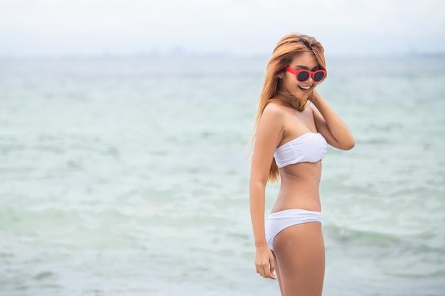 Loira linda garota em biquíni branco fica na praia.