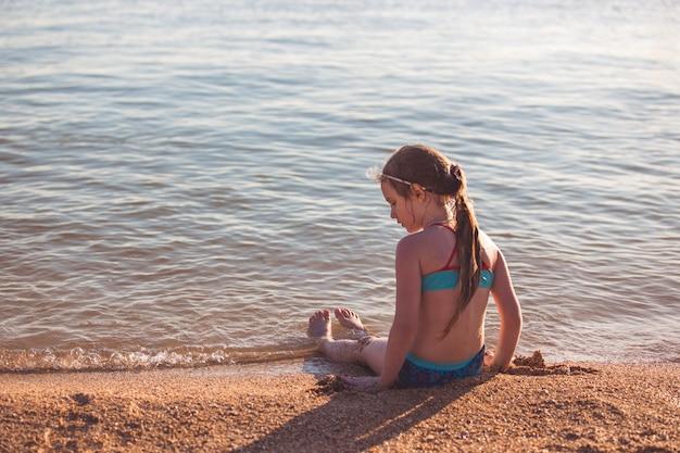 Loira linda menina de sete anos sentada na praia durante as férias.