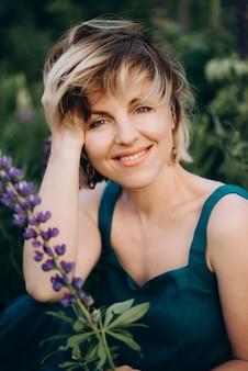 Loira linda mulher romântica em um campo de tremoços de flores roxas, sorrindo com uma flor.