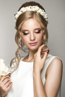 Loira linda na imagem da noiva com flores brancas na cabeça dela