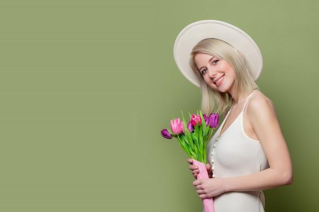 Loira linda no chapéu branco e vestido com tulipas