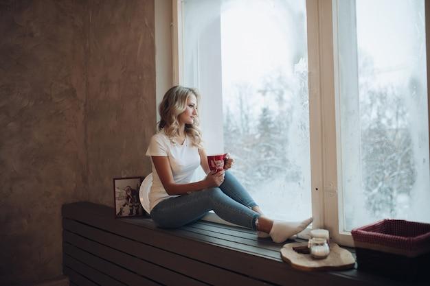 Loira linda sentada no peitoril da janela com caneca