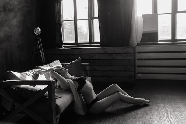 Loira linda sexy posando de lingerie preta e uma camisa branca