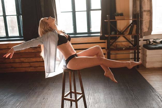 Loira linda sexy, posando de lingerie preta e uma camisa branca.