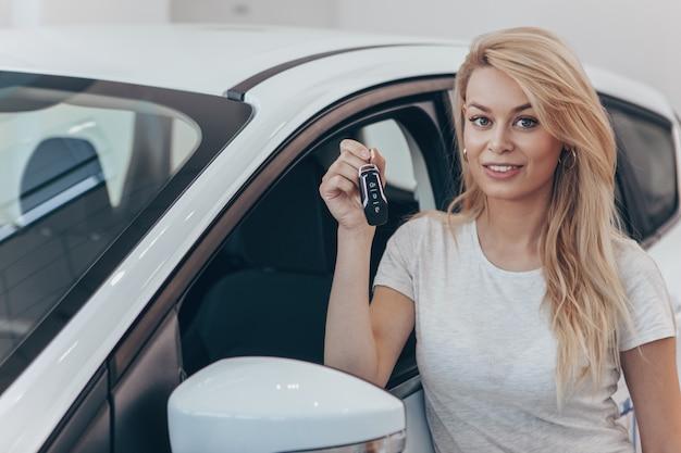 Loira linda sorrindo segurando as chaves do carro na concessionária.