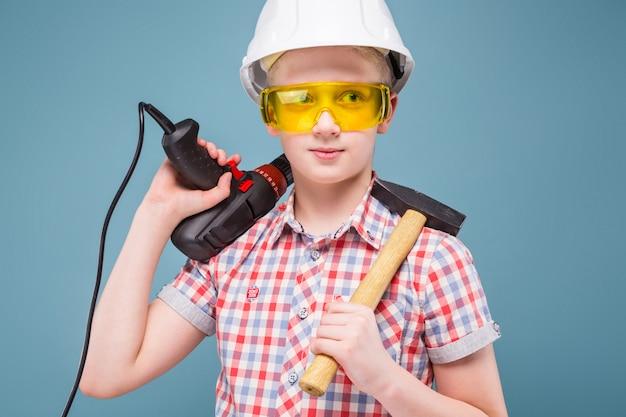 Loira loira adolescente no capacete de construção com uma chave de fenda e martelo