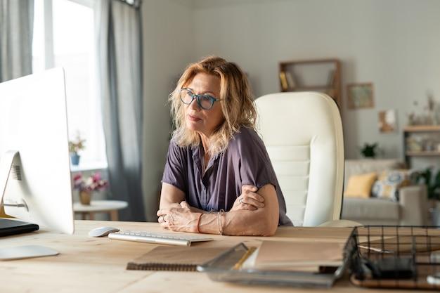 Loira madura designer feminina em trajes casuais, sentada na poltrona de couro branco perto da mesa e olhando para o monitor do computador enquanto trabalha