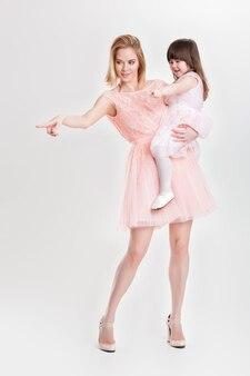 Loira mãe segurando uma filha pequena em um vestido rosa princesa em um fundo cinza. família
