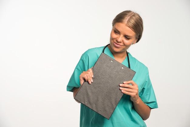 Loira médica de uniforme azul, segurando um livro de recibos e sorrindo.