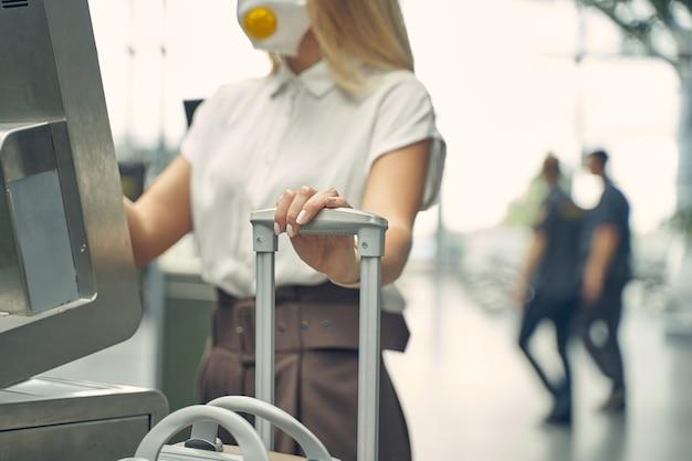 Loira meiga do sexo feminino usando roupas oficiais enquanto passa a manhã no aeroporto