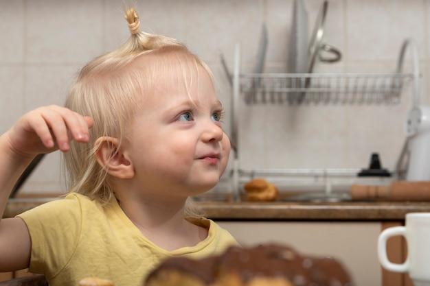 Loira menina bonitinha na cozinha quer sobremesa. criança feliz.