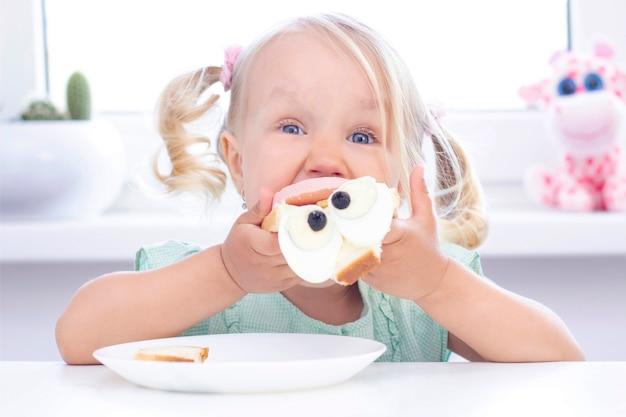 Loira menina criança come um sanduíche na mesa, em uma luz