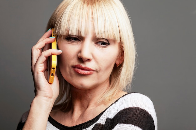 Loira moderna bonita com idade mulher com um telefone na mão.