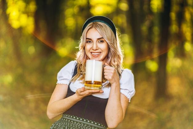 Loira muito feliz em vestidos casuais, tradicional festival, segurando a caneca de cerveja ao ar livre na floresta