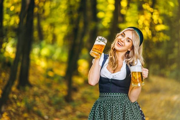 Loira muito feliz em vestidos casuais, tradicional festival, segurando duas canecas de cerveja ao ar livre na floresta