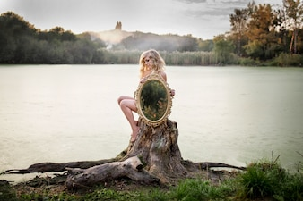 Loira mulher nua segura um espelho sentado diante de um lago coberto de névoa