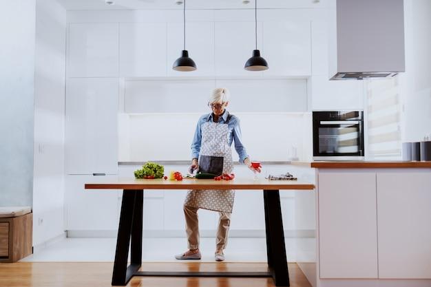 Loira mulher sênior em pé na cozinha, bebendo vinho e preparando a refeição saudável