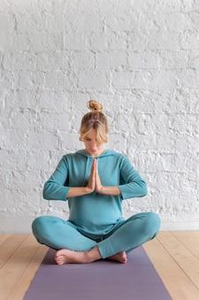 Loira no sportswear azul senta-se em um tapete no chão em uma posição de lótus, dobrando as palmas das mãos juntas