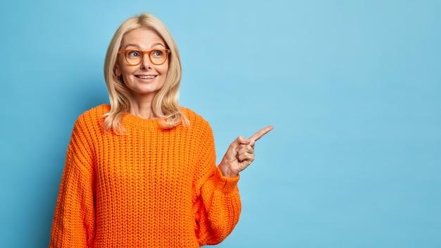 Loira pensativa de quarenta anos, europeia, usa óculos e suéter laranja de tricô apontando para o espaço da cópia