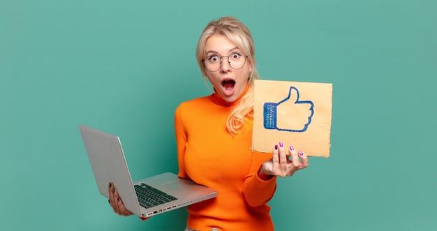 Loira pré-mulher com um laptop. conceito de mídia social